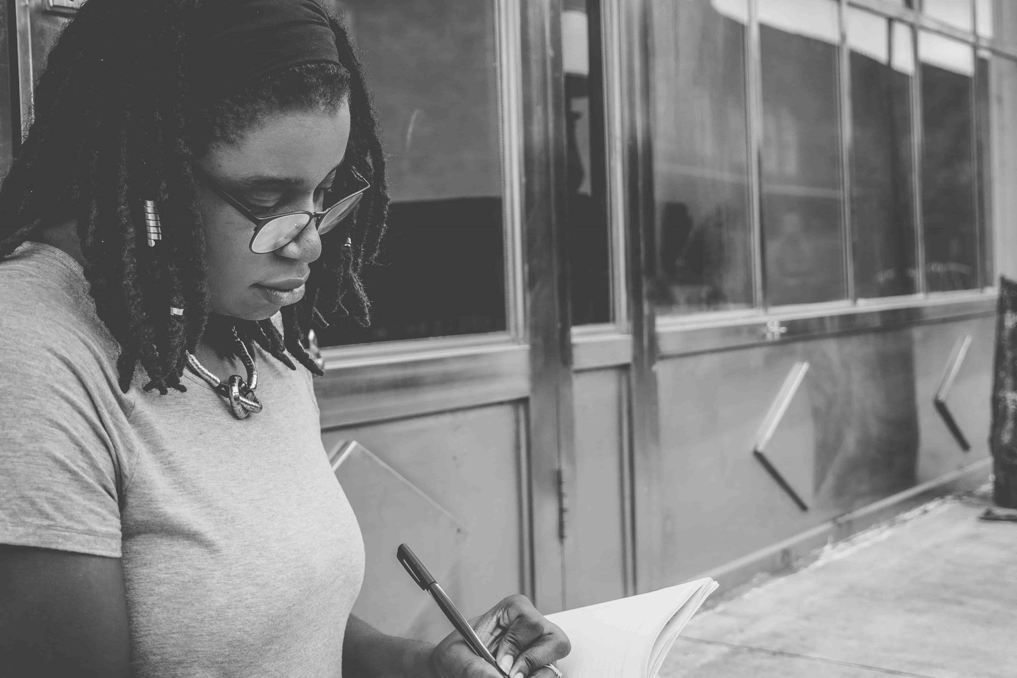 A girl with an eyeglass who is writing