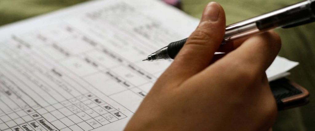 A person hand holding a ballpen with an answer sheet paper