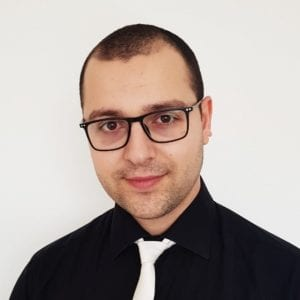 Man with glasses posing for a headshot photo