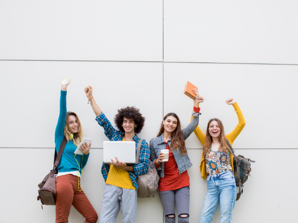 students posing on a wall
